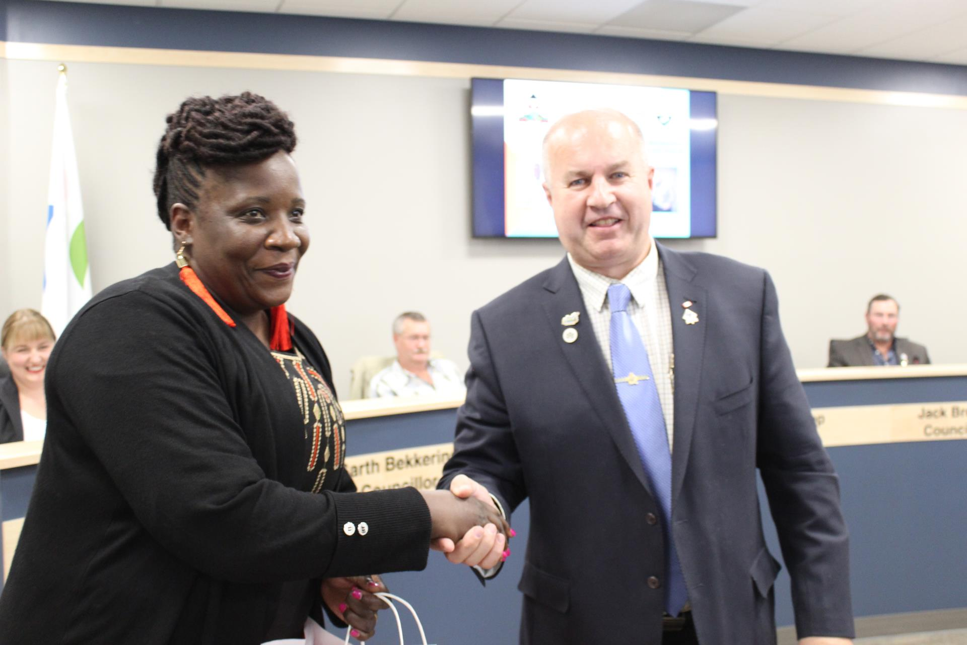 Mayor Prokop presents a gift to Ms. Pauline Odongo